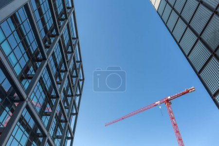 Red tower crane between buildings