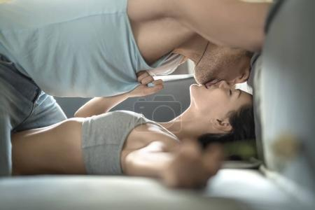 Photo for Kissing couple with closed eyes on the sofa. Girl in a gray top holds a flower in left hand. Guy in light sleeveless and blue jeans stands on the knees over her body. Indoors. Horizontal. - Royalty Free Image