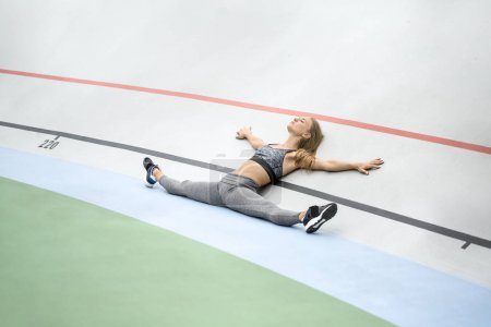 Photo for Cute girl with closed eyes lies at her back with outstretched legs and hands on the cycle track outdoors. She wears a gray sportswear with dark sneakers. Horizontal. - Royalty Free Image