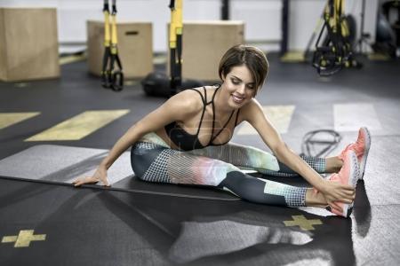 Photo pour Souriante fille est assise sur le tapis de fitness dans la salle de gym. Elle porte un pantalon coloré avec un haut noir et des baskets roses. Femme tient sa main gauche sur le pied droit et regarde vers le bas. Horizontal . - image libre de droit