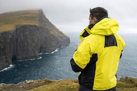 Guy on cliff on seashore