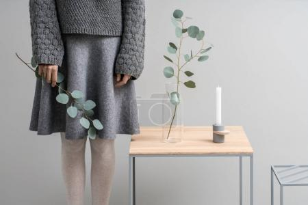Photo pour Femme avec branche verte dans la main dans le studio sur le fond mural gris. À côté d'elle, il y a deux supports en bois métallique avec une autre branche dans le vase en verre et le chandelier. Horizontal . - image libre de droit