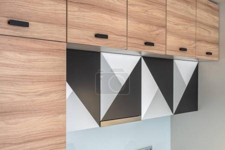 Photo pour Casiers en bois avec poignées noires sur la cuisine moderne. Il y a une hotte de cuisine et trois casiers avec des impressions géométriques noir-gris-blanc. Gros plan. Horizontal . - image libre de droit