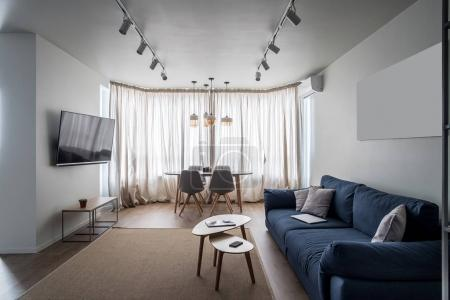 Photo for Trendy modern interior with white walls and a parquet with a carpet on the floor. There is a blue sofa with pillows, wooden tables, chairs, TV, stand with plant, window with curtains, hanging lamps. - Royalty Free Image