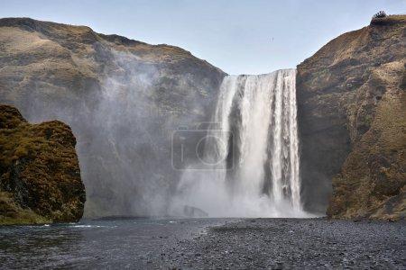Photo pour Paysage paisible en Islande avec une cascade qui tombe vers le bas de la falaise. Rivière a des côtes rocheuses et falaises couvertes par l'herbe fanée et moss. Il y a une terrasse d'observation sur le dessus. Horizontal. - image libre de droit