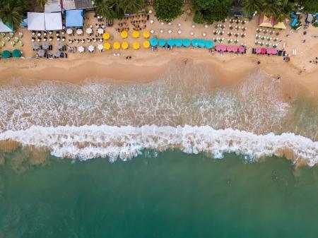 Photo pour Belle plage en tras sur le Sri Lanka. Là-dessus, il y a de nombreux parapluies multicolores avec transats, zones de café, se détendre les touristes. Photo aérienne de horizontal. - image libre de droit