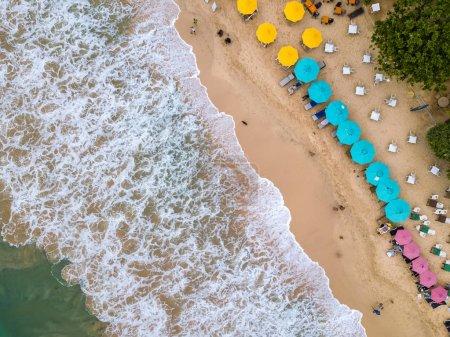 Photo pour Plage de sable de tras sur le Sri Lanka. Là-dessus, il y a de nombreux parapluies multicolores avec transats, zones de café, se détendre les touristes. Photo aérienne de horizontal. - image libre de droit