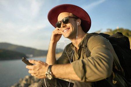 Photo pour Joli gars souriant dans des lunettes de soleil écoute de la musique tout en étant assis sur la falaise sur le fond ensoleillé de la baie de la mer. Il porte une chemise olive, un chapeau cramoisi, un jean foncé et un sac à dos. Horizontal . - image libre de droit