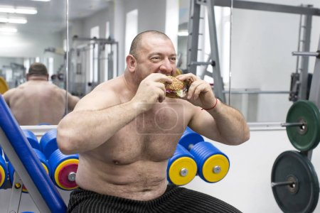 A big fat hungry man eats a hamburger with meat an...