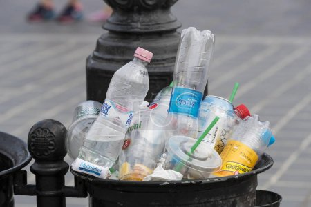 Street trash cans are filled with garbage cans with plastic bottles of scans up to the top.