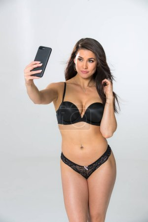 Photo for A gorgeous brunette model takes selfies in lingerie in a studio environment - Royalty Free Image