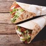 Burritos with bacon and fresh mix of salad close-u...