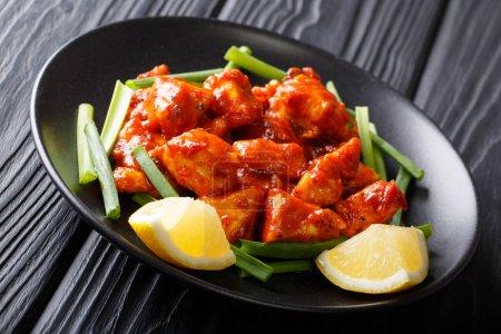 Photo pour Morceaux de poulet épicés en sauce rouge avec oignons verts et citron gros plan sur une assiette sur une table. horizonta - image libre de droit