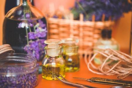 Photo pour Huile de lavande fraîche avec des fleurs fraîches dans le panier sur le fond orange - image libre de droit