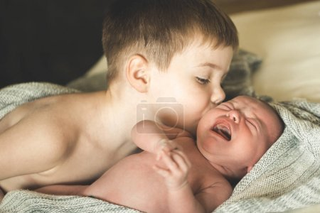 Two brothers are lying on the bed, the eldest is k...
