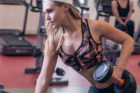 Body and mind workout in loft fitness studio. Closeup on fitness woman taking dumbbell from the floor in urban loft gym