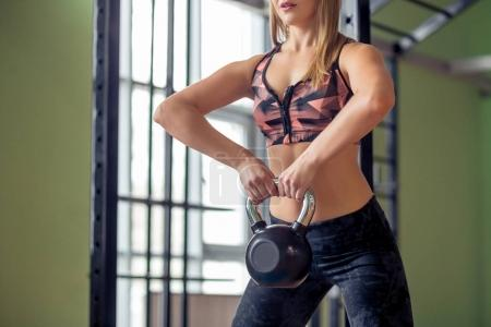 Fit people swinging kettlebell weights at the gym