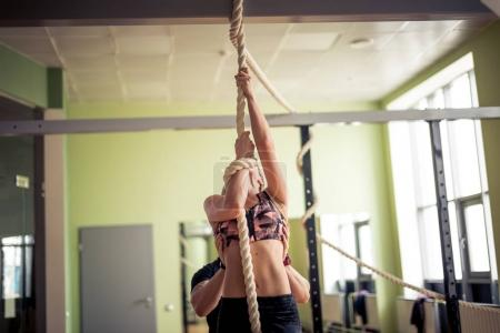 Male trainer assisting woman in rope climbing