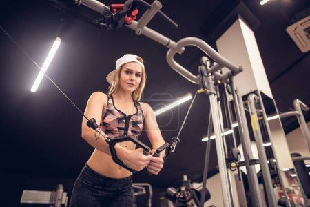 young fitness woman execute exercise with exercise-machine Cable Crossover in gym