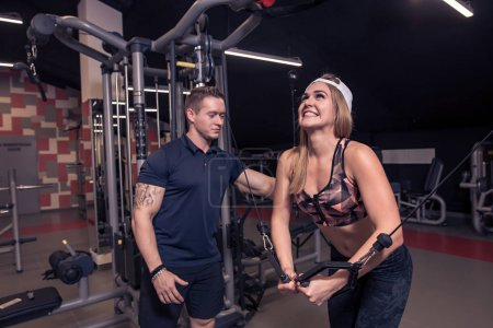 male trainer help young fitness woman execute exercise with exercise-machine Cable Crossover in gym, horizontal photo