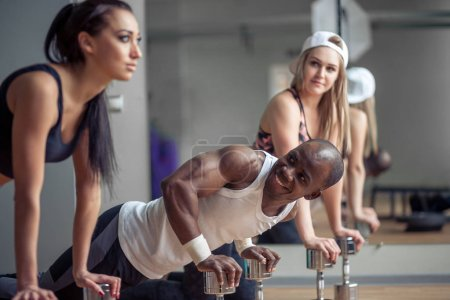 Side view of a group of fitness people doing push ups