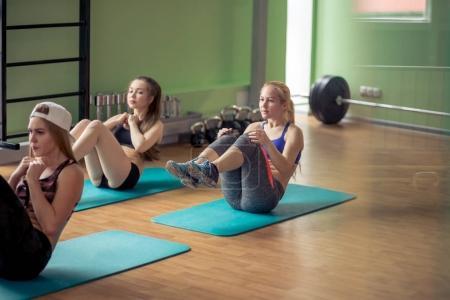 Photo pour Convient aux femmes qui font des sit-ups sur des tapis d'exercice au club de fitness - image libre de droit
