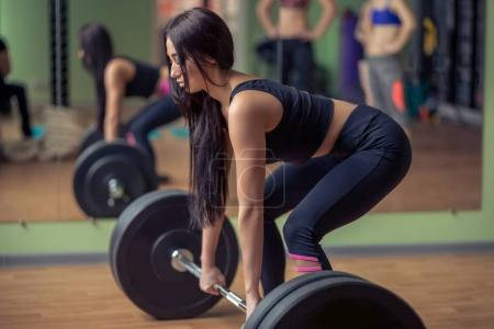 Full length of an fit young woman working out with a barbell at the gym. Bodybuilder female exercising at the gym.