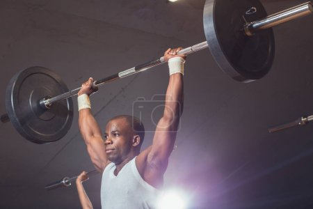 happy african man working out with barbell