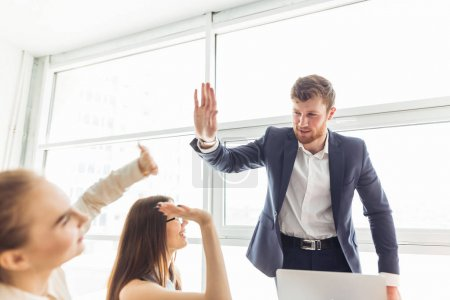 happy young business women and man doing high five in office