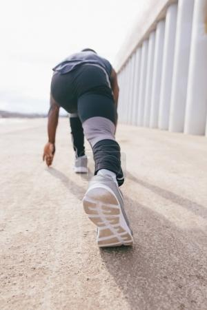 Athlete man in running start pose on the city street. Sport tight clothes