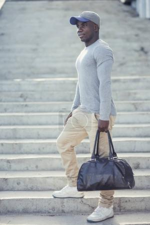 Photo for Portrait of attractive African athlete coming home after workout at fitness club, messaging via social networks. Healthy lifestyle concept - Royalty Free Image