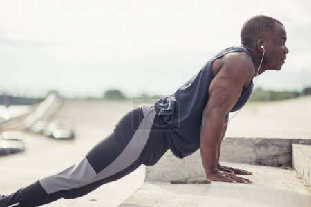 Young athletic man doing push-ups. Fitness model doing outdoor workout.