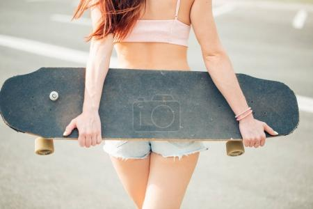 Young woman holding longboard on his back, rear view