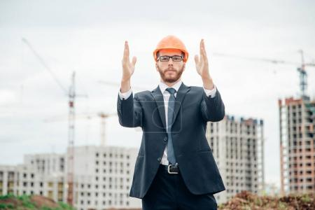 senior builder in hardhats pointing outdoors