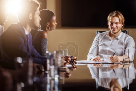 Team leader talking with coworkers in modern office