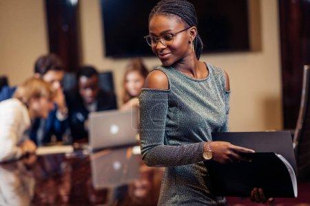 Foto de Joven mujer de negocios africana sonriendo a la cámara en la sala de juntas con colegas masculinos de fondo - Imagen libre de derechos