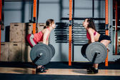 athletic woman lifting heavy barbells on shoulders in light spacious gym