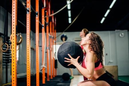 Photo pour Concept de fitness, de sport et d'exercice - deux femmes avec entraînement de médecine-ball en salle de gym - image libre de droit