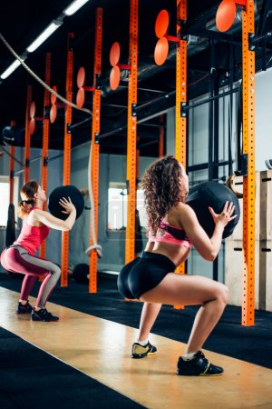 fitness and exercising concept - two woman with medicine balls training in gym