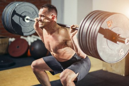 Muscular man training squats with barbells on shoulders