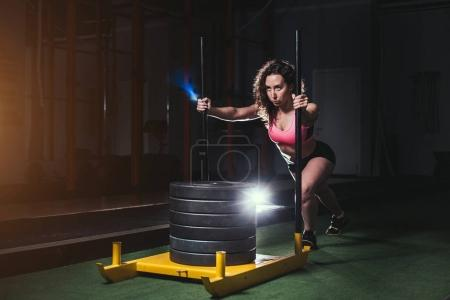 female pushing the prowler exercise equipment on artificial grass turf