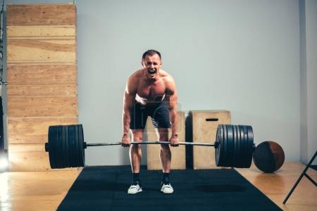 man doing deadlift barbell over his head in modern fitness center.