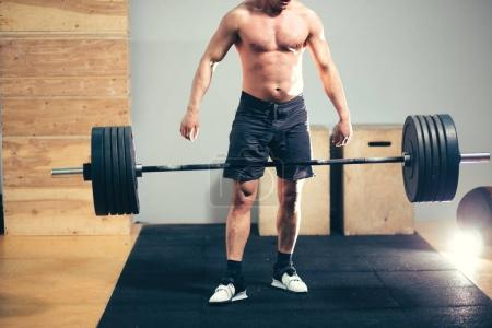 Bodybuilder drops heavy barbell weights during training