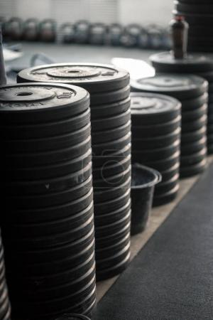 stack of barbell plates stacked on movable pegs on wheels in gym