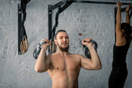 man lifting two kettlebell workout exercise at gym