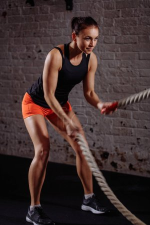 athletic woman doing some cross fit exercises with battle rope indoor