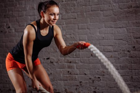 close up photo of Athletic woman doing battle rope exercises at gym