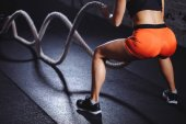 rear view of tonned woman training with battle rope in cross fit gym