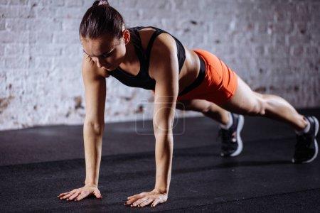Photo pour Jeune belle femme en sportswear faire planche tandis que trainnig à cross fit gym - image libre de droit