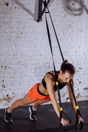 Women doing push ups training arms with trx straps in gym